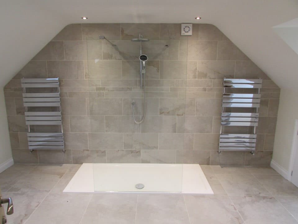 Glass shower in bathroom with tiles and heaters